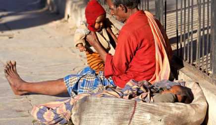 A low-caste man with his two children begs on the streets